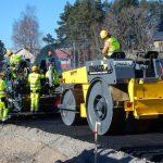 Uuden asfaltin laittaminen asfalttilevittimellä ja asfalttijyrän tasoittamana